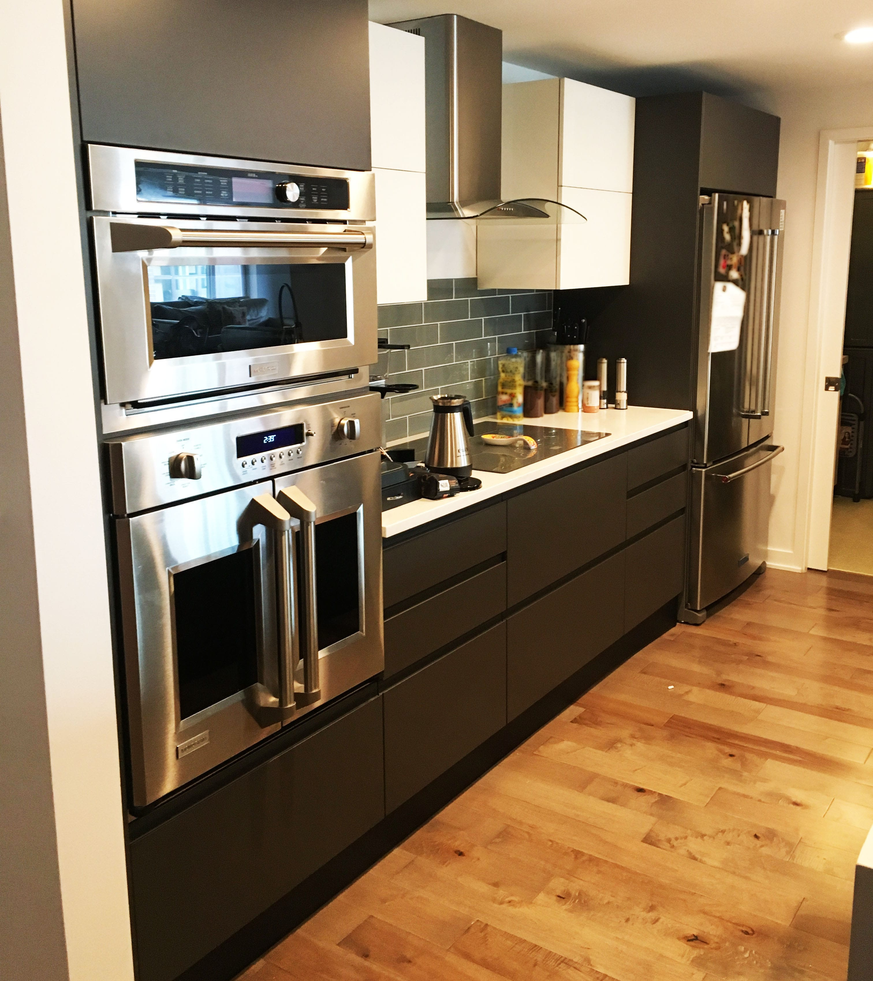 Updated Kitchen using Solid Black Cabinetry, Stainless-Steel Appliances, and Refinished Hardwood Floor