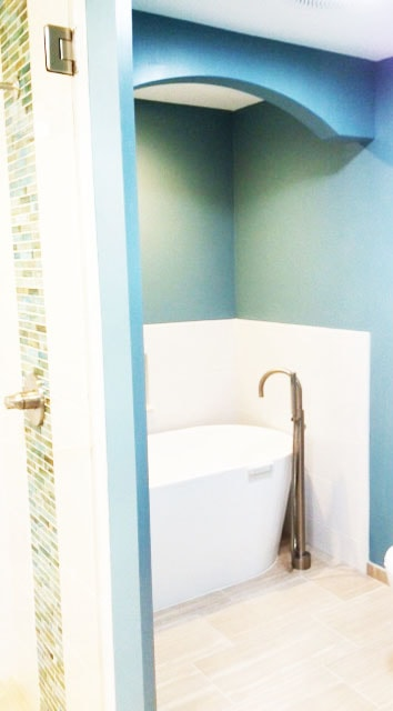 Free Standing Bathtub Renovation with Ceramic Tile Flooring and Glass Accent Wall