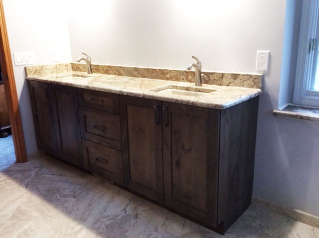 Granite Bathroom Countertop with Dual Sinks and Reclaimed Wood Cabinets