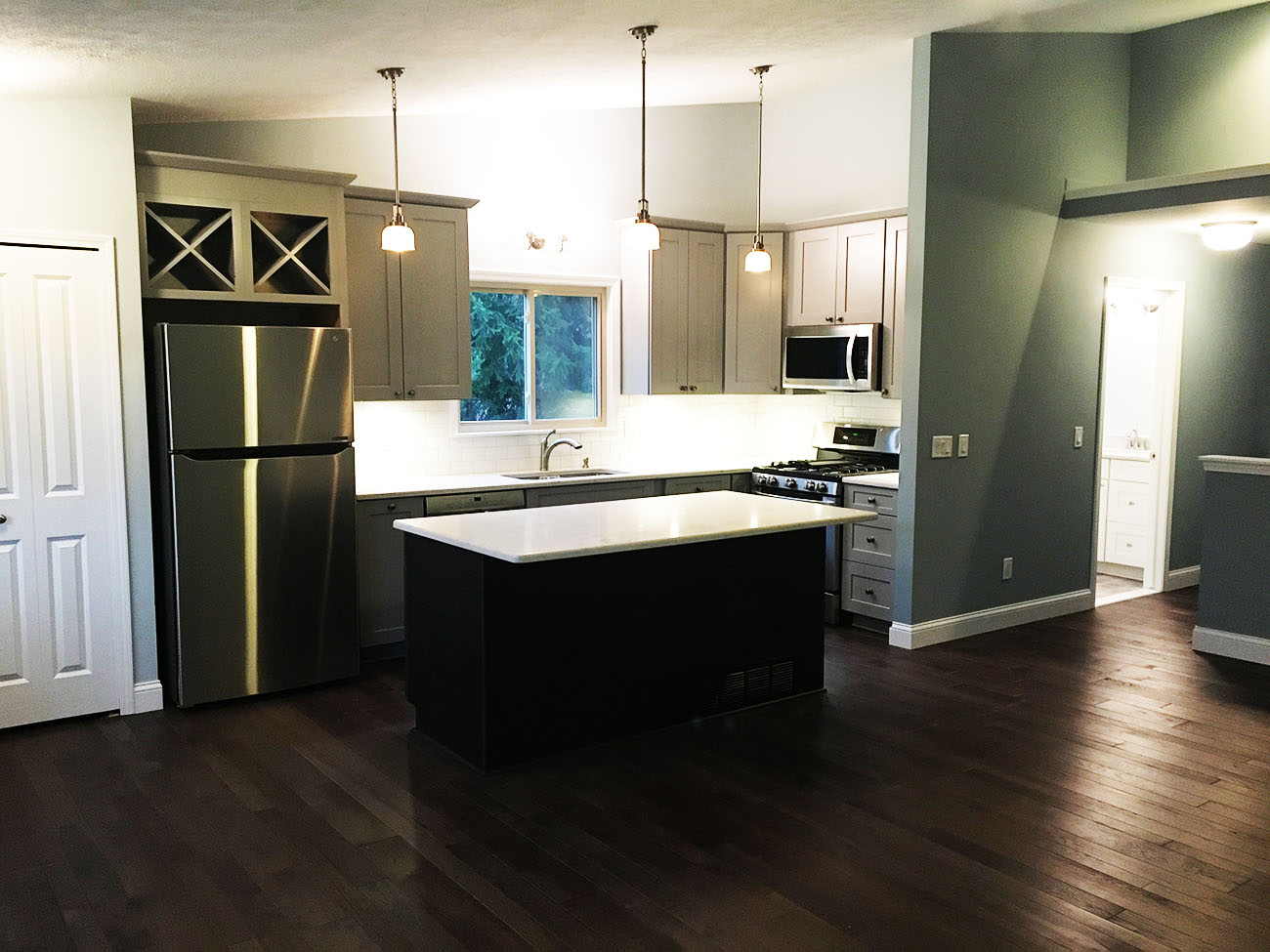 Dark Hard Wood Kitchen Flooring with Renovated Cabinets and Kitchen Island